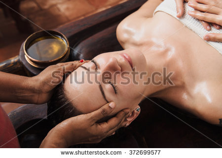 stock-photo-ayurvedic-face-massage-with-oil-on-the-wooden-table-in-traditional-style-made-by-asian-women-372699577